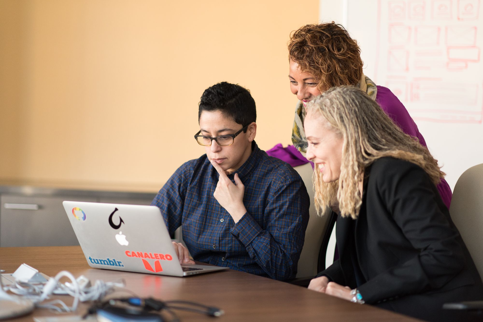 three people look at a laptop to collaborate
