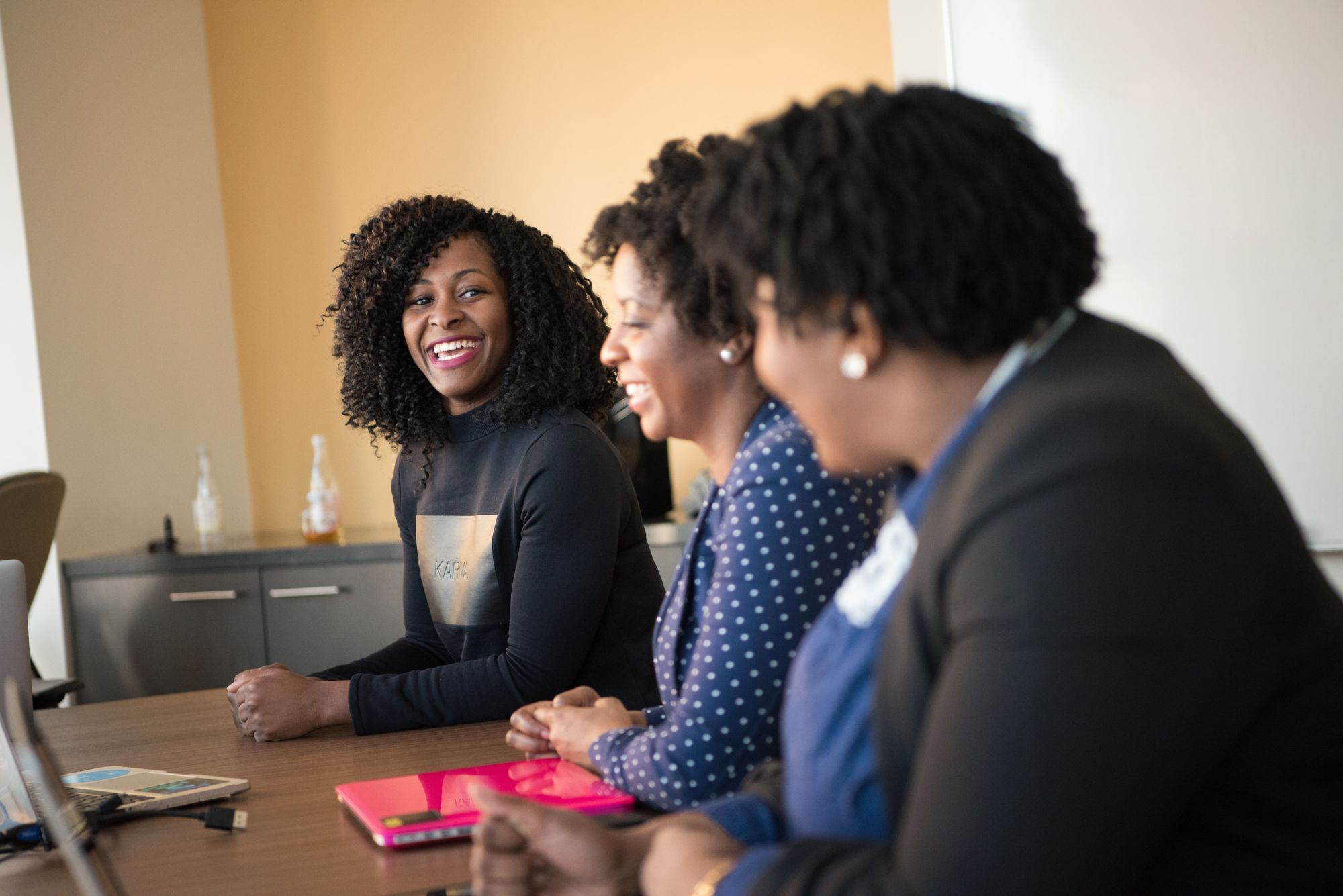 three women sit at a conference table