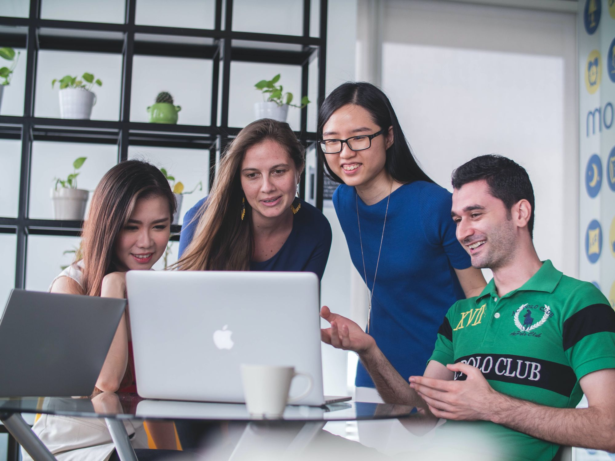 a group of four friends crowd around a computer screen